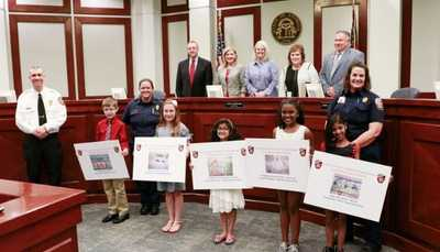 fire safety poster contest winners stand holding their posters in a court room